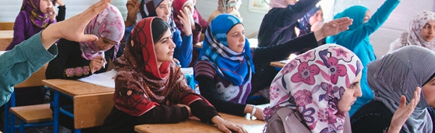 Malala sits in class, surrounded by students with their hands raised to answer a question.
